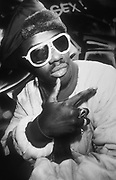 Fab Five Freddy posing for the camera in front of wall of graffiti, wearing white-rimmed sunglasses and furry hat, U.S.A, 1980s.