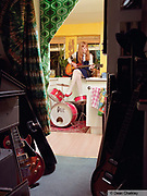 Stephanie Something, sat in her kitchen playing guitar, wearing Mod, retro styles, Southend, UK 2006