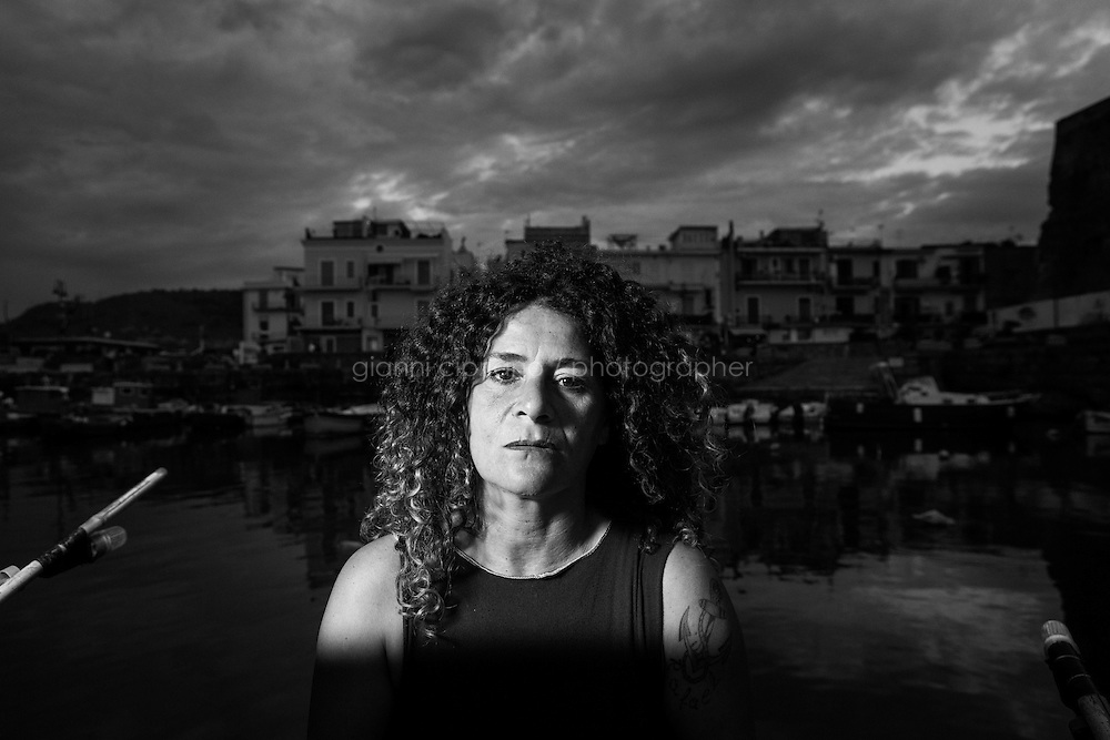 POZZUOLI, ITALY - 8 OCTOBER 2016: Cristina Pinto (47), also known as &quot;Nikita&quot;, a former Camorra killer turned into a fisherwoman, poses for a portrait by her fishing boat in the port of Pozzuoli, a city of the Metropolitan area of Naples, Italy, on October 8th 2016.<br /> <br /> Cristina Pinto started her criminal career at 16 with armed robberies. By the time she turned 20 years old, she became the bodyguard of Camorra boss Mario Perrella as well as the first woman to become a killer for the criminal organization. When she was arrested in 1992, at the age of 22 years old, she was charged and sentenced for at least three homicides and for criminal conspiracy. She spent the following 22 years in prison. When released, she became a fisherwoman. She now fishes with her partner Raffaele.