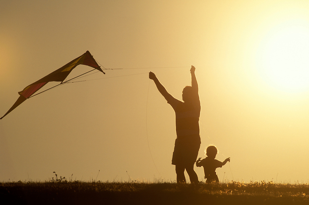 USA, Washington, Seattle, Father and son launch kite from hilltop at Sand Point Park by  summer sunset