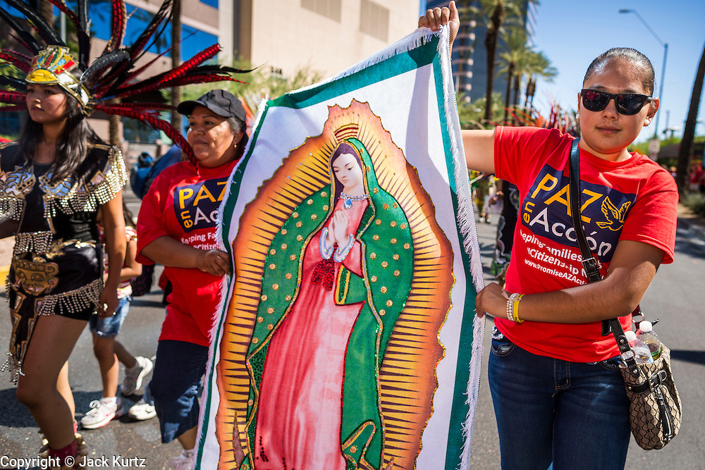 05 OCTOBER 2013 - PHOENIX, ARIZONA: Women carry a shroud of the Virgin of Guadalupe during an immigration march in Phoenix. More than 1,000 people marched through downtown Phoenix Saturday to demonstrate for the DREAM Act and immigration reform. It was a part of the National Day of Dignity and Respect organized by the Action Network.    PHOTO BY JACK KURTZ
