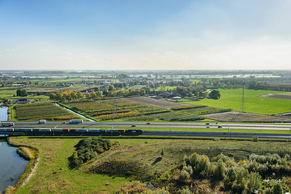 Nederland, Gelderland, Betuwe, 24-10-2013; Betuweroute, ter hoogte van Echteld. De goederenspoorlijn loopt parallel aan autosnelweg A15. De goederentrein is onderweg naar de haven van Rotterdam. Naast de weg en het spoor boomkwekerijen.<br /> Betuweroute, railway from Rotterdam to Germany, near Echteld. The freight railway runs parallel to highway A15. The freight is on its way to the port of Rotterdam.<br /> luchtfoto (toeslag op standaard tarieven);<br /> aerial photo (additional fee required);<br /> copyright foto/photo Siebe Swart.