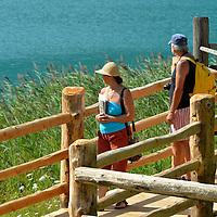 Turisti in visita al parco del Museo delle Palafitte; sullo sfondo le canne palustri e il Lago di Ledro
