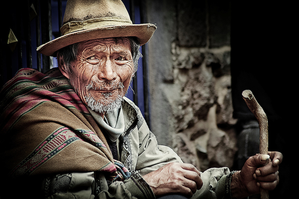 Old, blind man begging in a street market, Peru.