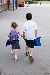 Brother and sister holding hands walking home from school,