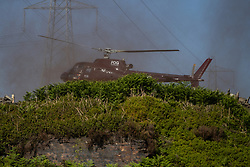 """© Licensed to London News Pictures . 28/06/2018 . Saddleworth , UK . A helicopter lands at Higher Swineshaw Reservoir . The army are being called in to support fire-fighters , who continue to work to contain large wildfires spreading across Saddleworth Moor and affecting people across Manchester and surrounding towns . Very high temperatures , winds and dry peat are hampering efforts to contain the fire , described as """" unprecedented """" by police and reported to be the largest in living memory . Photo credit: Joel Goodman/LNP"""