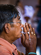 18 SEPTEMBER 2016 - BANGKOK, THAILAND:  A man prays with a rosary during the 100th anniversary mass at Santa Cruz Church. Santa Cruz Church was establised in 1769 to serve Portuguese soldiers in the employ of King Taksin, who reestablished the Siamese (Thai) empire after the Burmese sacked the ancient Siamese capital of Ayutthaya. The church was one of the first Catholic churches in Bangkok and is one of the most historic Catholic churches in Thailand. The first sanctuary was a simple wood and thatch structure and burned down in the 1800s. The church is in its third sanctuary and was designed in a Renaissance / Neo-Classical style. It was consecrated in September, 1916. The church, located on the Chao Phraya River, serves as a landmark for central Bangkok.      PHOTO BY JACK KURTZ