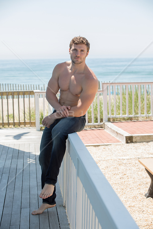 shirtless muscular man sitting on a deck by the ocean