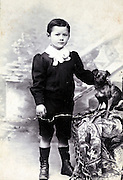 studio portrait of a young child with small pet dog 1920s