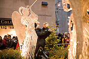A tourist takes photographs of the Rickefeller Christmas Tree from the Promenade.
