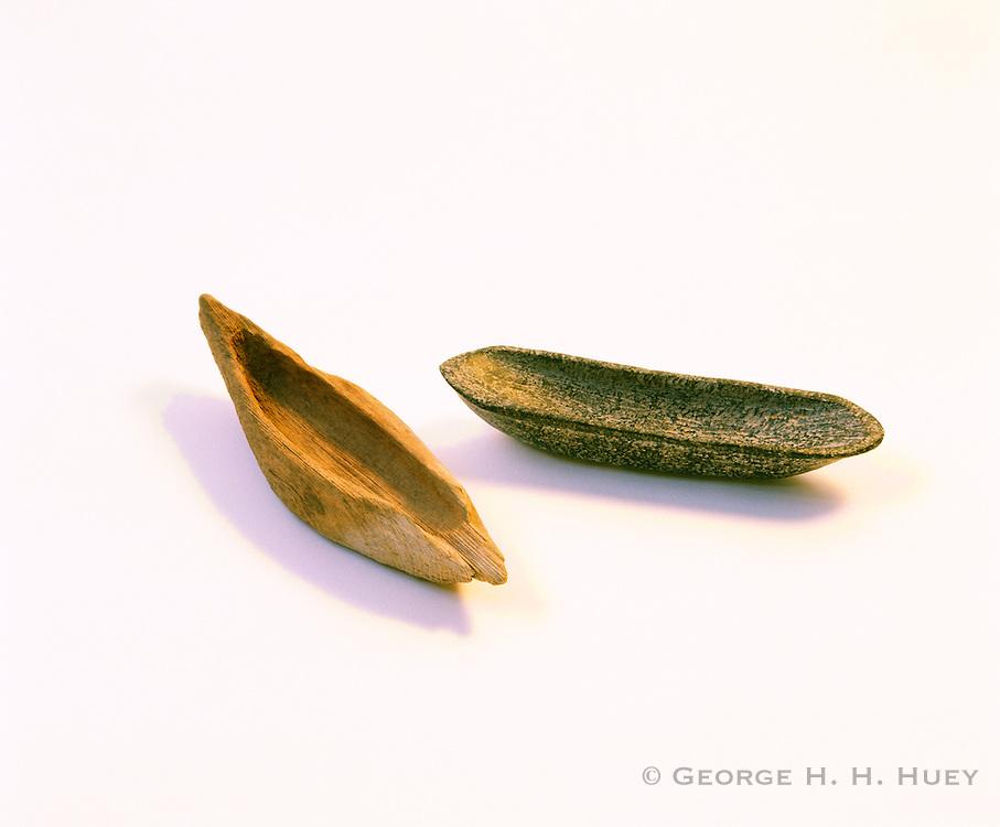0603-7004B ~ Copyright: George H. H. Huey ~ Chumash Indian 'tomol' [canoe] effigies, in wood and stone. About 5 inches long. Santa Barbara Museum of Natural History, California.