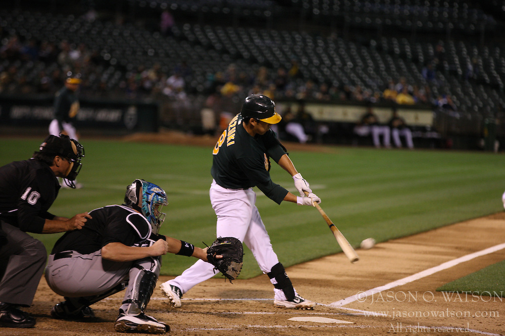 June 28, 2011; Oakland, CA, USA;  Oakland Athletics catcher Kurt Suzuki (8) hits an RBI sacrifice fly against the Florida Marlins during the second inning at the O.co Coliseum.