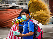 24 JANUARY 2018 - LIGAO, ALBAY, PHILIPPINES: A broom vender with a breathing filter walks down a street in Ligao during a volcanic ash fall . The Mayon volcano continued to erupt Tuesday night and Wednesday forcing the Albay provincial government to order more evacuations. By Wednesday evening (Philippine time) more than 60,000 people had been evacuated from communities around the volcano to shelters outside of the 8 kilometer danger zone. Additionally, ash falls continued to disrupt life beyond the danger zones. Several airports in the region, including the airport in Legazpi, the busiest airport in the region, are closed indefinitely because of the amount of ash the volcano has thrown into the air.   PHOTO BY JACK KURTZ