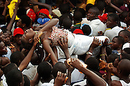 A woman is helped to the stage after she passed out in the heat of the pressing crowd at a rally for presidential candidate George Weah.
