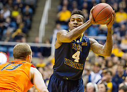 West Virginia Mountaineers guard Daxter Miles Jr. (4) looks to pass to a teammate against the Oklahoma State Cowboys during the second half at the WVU Coliseum.