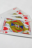 Ace, King, Queen and Jack of Clubs playing cards in a fan shape on a plain background<br />