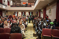 SLIEMA, MALTA - 8 FEBRUARY 2016: Sub-Saharan migrants from the Hal Far camp are here among the Maltese audience before the touring Hamlet, performed by the Shakespeare's Globe theatre company, starts at the Salesian Theatre in Sliema, Malta, on February 8th 2016.<br /> <br /> The touring Hamlet, performed by the Shakespeare's Globe theatre company, is part of the Globe to Globe tour that set off in April 2014 (on the 450th anniversary of Shakespeare's birth) with the ambitious intention of visiting every country in the world over 2 years. The crew is composed of a total of sixteen men and women: four stage managers and twelve twelve actors  actors perform over two dozen parts on a stripped-down wooden stage. So far Hamlet has been performed in over 150 countries, to more than 100,000 people and travelled over 150,000 miles. The tour was granted UNESCO patronage for its engagement with local communities and its promotion of cultural education. Hamlet was also played for many dsiplaced people around the world. It was performed in the Zaatari camp on the border between Syria and Jordan, for Central African Republic refugees in Cameroon, and for Yemeni people in Djibouti. On February 3rd it was performed to about 300 refugees in Calais at the camp known as the Jungle.