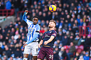 Adama Diakhaby of Huddersfield Town (11) rises above cShkodran Mustafi of Arsenal (20) during the Premier League match between Huddersfield Town and Arsenal at the John Smiths Stadium, Huddersfield, England on 9 February 2019.