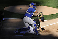CHICAGO - SEPTEMBER 12:  Omar Vizquel #11 of the Chicago White Sox scores the go-ahead run on a single by Paul Konerko as the ball skips by catcher Brayan Pena #27 of the Kansas City Royals in the sixth inning on September 12, 2010 at U.S. Cellular Field in Chicago, Illinois.  The White Sox defeated the Royals 12-6.  (Photo by Ron Vesely)