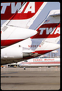 Tails of parked TWA jets line up outside concourse at Lambert International Airport; St. Louis Missouri