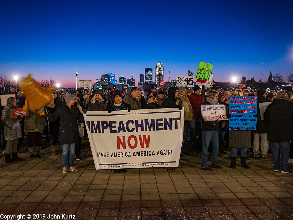 17 DECEMBER 2019 - DES MOINES, IOWA: With the Des Moines skyline behind them, about 300 people stood in front of the Iowa State Capitol in Des Moines in near freezing weather Tuesday evening to call for President Donald Trump's impeachment. The rally, and others like it around the US, come on the eve of an impeachment vote in the US House of Representatives.     PHOTO BY JACK KURTZ