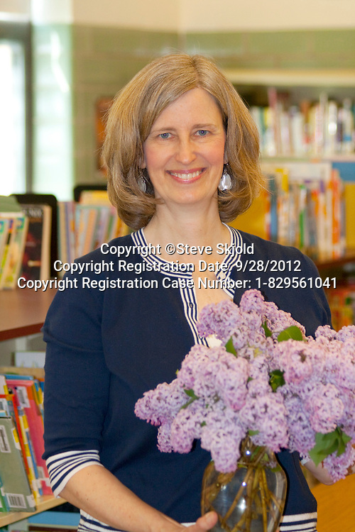 Happy first grade teacher holding a bouquet of purple lilacs in her classroom. Horace Mann School St Paul Minnesota MN USA
