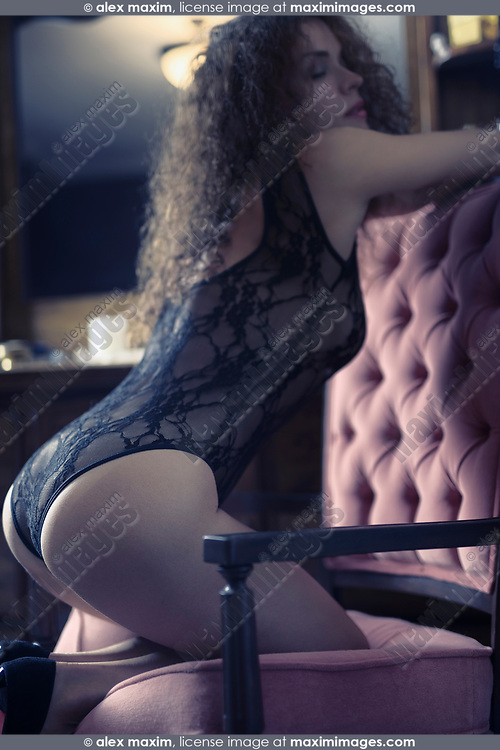 Artistic boudoir portrait of a sexy beautiful woman standing on her knees in a chair leaning against the backrest with her body arched in a seductive curve by a dresser mirror with sensual expression wearing lacy underwear. Vintage retro French style.