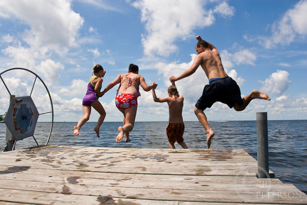 four children jumping off a wooden dock into the lake on a sunny summer day