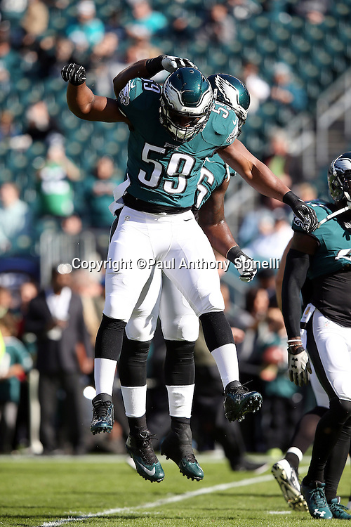 Philadelphia Eagles inside linebacker DeMeco Ryans (59) leaps and celebrates with a teammate during the 2015 week 10 regular season NFL football game against the Miami Dolphins on Sunday, Nov. 15, 2015 in Philadelphia. The Dolphins won the game 20-19. (©Paul Anthony Spinelli)