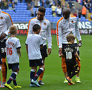 Benik Afobe and Scott Golbourne shake hands with the mascots during the Sky Bet Championship match between Bolton Wanderers and Wolverhampton Wanderers at the Macron Stadium, Bolton, England on 12 September 2015. Photo by Mark Pollitt.