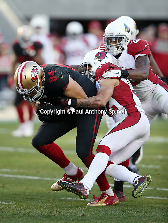 San Francisco 49ers tight end Blake Bell (84) gets tackled by Arizona Cardinals free safety Tyrann Mathieu (32) after catching a third quarter pass during the 2015 week 12 regular season NFL football game against the Arizona Cardinals on Sunday, Nov. 29, 2015 in Santa Clara, Calif. The Cardinals won the game 19-13. (©Paul Anthony Spinelli)
