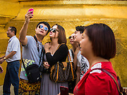"15 OCTOBER 2014 - BANGKOK, THAILAND:  Japanese tourists take a ""selfie"" in the Grand Palace in Bangkok. The number of tourists arriving in Thailand in July fell 10.9 per cent from a year earlier, according to data from the Department of Tourism. The drop in arrivals is being blamed on continued uncertainty about Thailand's political situation. The tourist sector accounts for about 10 per cent of the Thai economy and suffered its biggest drop in visitors in June - the first full month after the army took power on May 22. Arrivals for the year to date are down 10.7% over the same period last year.   PHOTO BY JACK KURTZ"