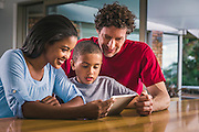 Multi-ethnic family using digital tablet at table in house