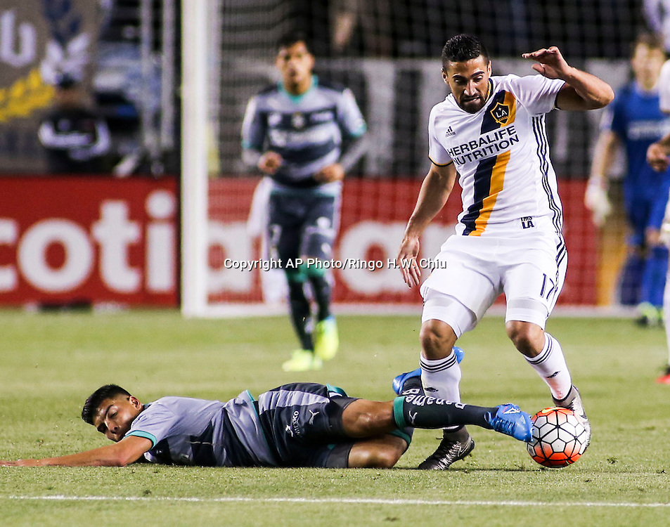 Santos Laguna forward Luis Angel Mendoza, left, slides into the ball against Los Angeles Galaxy midfielder Sebastian Lletget during the second half of a CONCACAF Champions League quarter final game in Carson, Calif., Wednesday, Feb. 24, 2016. The game ended in a 0-0 draw. (AP Photo/Ringo H.W. Chiu)
