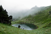 high up mountain lake with low clouds and hikers France Ariege