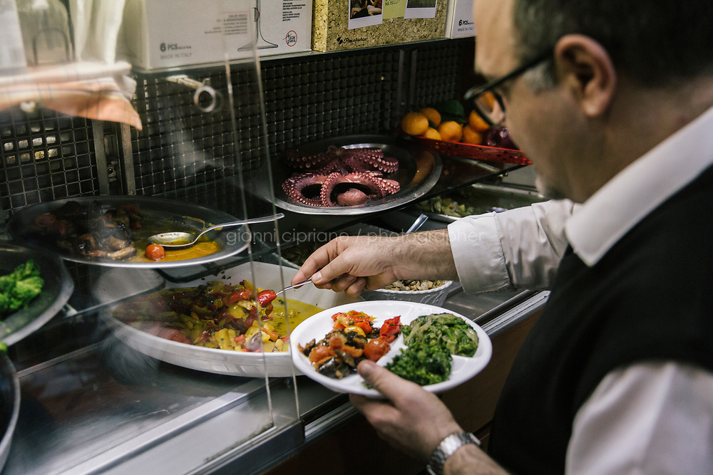 NAPLES, ITALY - 20 MARCH 2018: Vincenzo, a waiter of the Pizzeria e Trattoria Vigliena, grabs a side dish of endives, peppers, eggplants and tomotoes for customers in Naples, Italy, on March 20th 2018.<br /> <br /> Pizzeria e Trattoria Vigliena is a restaurant outside of the city center and adjacent to the port. At lunch, the place is packed with workers from the docks and ship owners and workers from the recently built Marina Vigliena.<br /> <br /> The restaurant is owned by Raffaele Esposito, Concetta&rsquo;s son and the third generation of a family of chefs who founded this restaurant in the middle of the 20th century