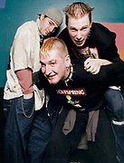 Three young men clowning around and posing.
