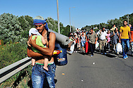 Syrian refugee supporting his baby's head as he carrys him along the highway, with other refugees, several kilometres after leaving Budapest. Thousands of refugees, mostly from Syria, had been stranded for days in Budapest at the city's main Keleti train station. The government had closed the borders with Western Europe to them, and cancelled all trains that might take them to Germany and beyond. On Friday, in a gesture of defiance and frustration, hundreds of refugees set out to walk to Vienna, a distance of about 250 kilometres. In reaction, in the night, the Hungarian government changed policy and brought refugees to the border with Austria, not only those on the road, but also those at Keleti station and others being held in various camps.