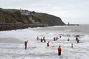 Closely watched by life guards locals enter the sea for the 2016 Folkestone Lions club boxing day dip.  An annual fancy dress fundraising event, Sunny Sands, Folkestone. UK
