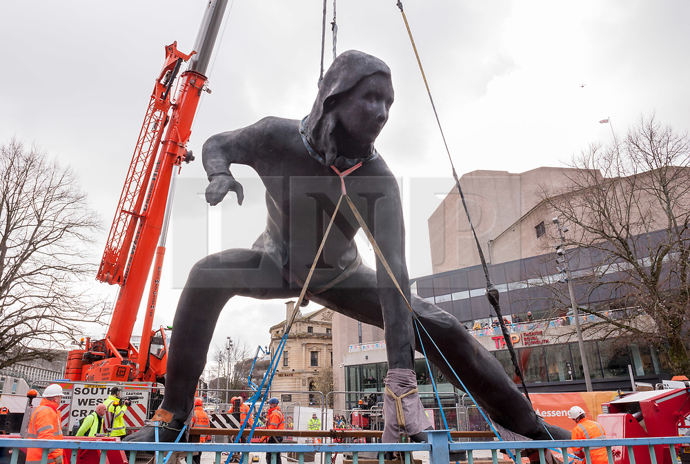 """© Licensed to London News Pictures. 18/03/2019. Plymouth, Devon, UK. """"Messenger"""", the largest bronze sculpture ever to be cast in the UK, is transported through Plymouth city centre before being installed at the Theatre Royal in Plymouth City Centre. It was brought into Plymouth by barge across Plymouth Sound. Weighing in at nine and a half tonnes with a height of seven metres (23ft) and nine metres (30ft) wide, with a volume of 25.6 metres cubed, """"Messenger"""" will be the size of two double decker buses and is the largest lost-wax cast bronze sculpture ever to be cast in the UK, a painstaking process that has taken over two years. """"Messenger"""" is the work of the acclaimed sculptor Joseph Hillier and has been created using 3D scans from the body of a young actor in mid-performance in Theatre Royal Plymouth and Frantic Assembly's production of Othello in 2014. A monument to the physical expression of theatre, """"Messenger"""" is a movement suspended in time that embodies the energy and creativity at the heart of the Theatre Royal and cultural life in Plymouth and aims to celebrate creativity as a dynamic catalyst for change. Plymouth is undergoing massive regeneration and the installation of the sculpture is is a prelude to the Mayflower 2020 celebrations. Messenger was cast at the Castle Fine Arts Foundry in the Welsh village of Llanrhaeadr-Ym-Mochnant, using the ancient technique of lost wax casting. Made from over 200 bronze panels, each section of the sculpture was cast individually before being welded together by over 30 master craftsmen at the foundry. Photo credit: Simon Chapman/LNP"""