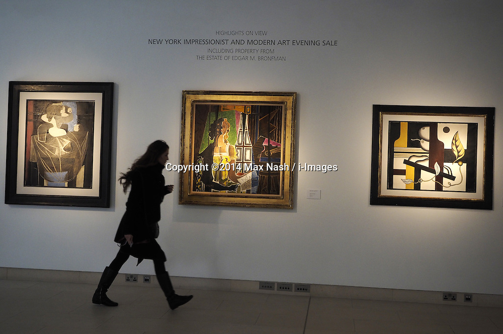 A Christie's employee walks past ( left to right) Pablo Picasso's 1925, Nature morte au filet de peche (estimated at $6-9 million), George Braque's 1939,'Le Modele', estimated $8-12million,Fernand Leger's,'Nature Morte(les fruits),estimated $2.5-3.5 million, at Christies Impressionist and Modern Art. display of highlights for the upcoming New York auction on May 6, 2014. Photo taken in London, United Kingdom. Friday, 28th March 2014. Picture by Max Nash / i-Images