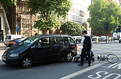 A policeman comes to help a female cyclist knocked over by a vehicle outside Westminster Magistrates Court in London, United Kingdom, Friday August 23, 2013. Picture by Max Nash / i-Images