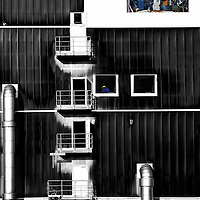 """The collage of an industrial building with workshops and ventilation pipes with the mosaic painting """"Man conquers the cosmos"""" of FRITZ EISEL."""