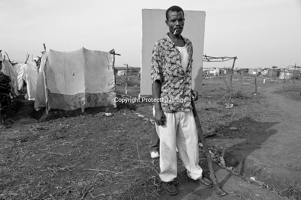 """Reginald Daphnis, 32 was at home on his bed when the quake hit, killing his five-year-old son Stephen. He and his remaining family moved out to Canaan II soon after and have been here for 6 weeks. He's laboring now to build a sturdier home. How long does he plan to stay? """"Until I die,"""" he deadpans. """"I don't know. I'm going to build a shelter here. Build it out of wood and cover it with cardboard and blankets."""""""