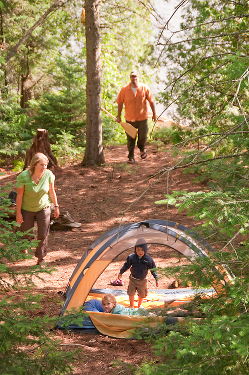 A young family plays in a tent while camping at Craig Lake State Park near Michigamme Michigan.