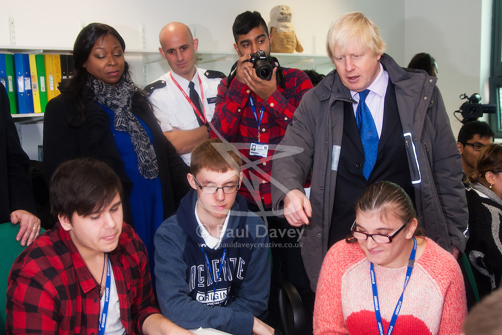 Ealing, London, December 9th 2014. Mayor of London Boris Johnson visits Ealing, Hammersmith and Fulham College accompanied by   Deputy Mayor for Policing and Crime Stephen Greenhalgh to launch a new initiative to increase black and ethnic minority applicants to the Met. PICTURED: Boris Johnson chats with students.