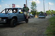 Demolition derby contestant proceed down pit lane before entering into a routine check stop to ensure race worthiness of the vehicles at the Summitt County Fairgrounds, Thursday, July 26, 2016 in Tallmadge, Ohio.