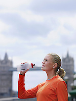 Woman drinking water in front of Tower Bridge England London