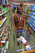 "A traditionally dressed Himba woman shops for staples and soda pop with her child in a supermarket in Opuwo, a town well known for cultural tourism in northwestern Namibia, after receiving money from a tourist in exchange for a photograph.  Like most traditional Himba women, she covers herself from head to toe with an ochre powder and cow butter blend. Some Himba are turning to tourism to kick-start their entry into the cash economy, setting up demonstration villages advertising ""The Real Himba."""