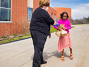 22 APRIL 2020 - DES MOINES, IOWA: SUSAN AYALA hands a grab and go meal to a student at Edmunds Elementary School. Schools in Iowa are closed for the rest of the school year because of the COVID-19 (Coronavirus/SAR-CoV-2) pandemic. Des Moines Public Schools expanded their school lunch and distance learning efforts this week. Lunches are being distributed at all of the district's elementary and middle schools and officials have started distributing computers so students can participate in distance learning. The meal distribution was done according to social distancing guidelines.           PHOTO BY JACK KURTZ